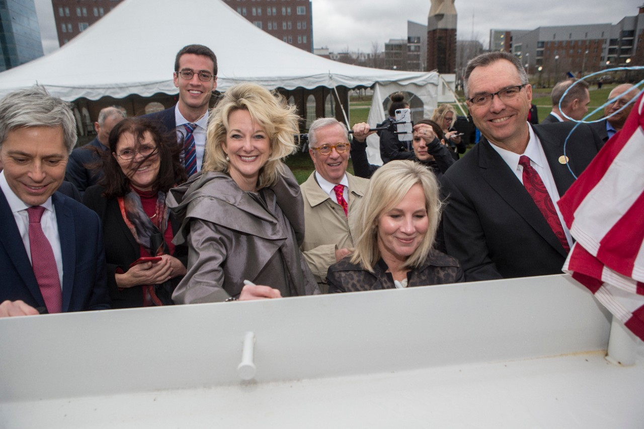 Guests smile as they sign the beam.