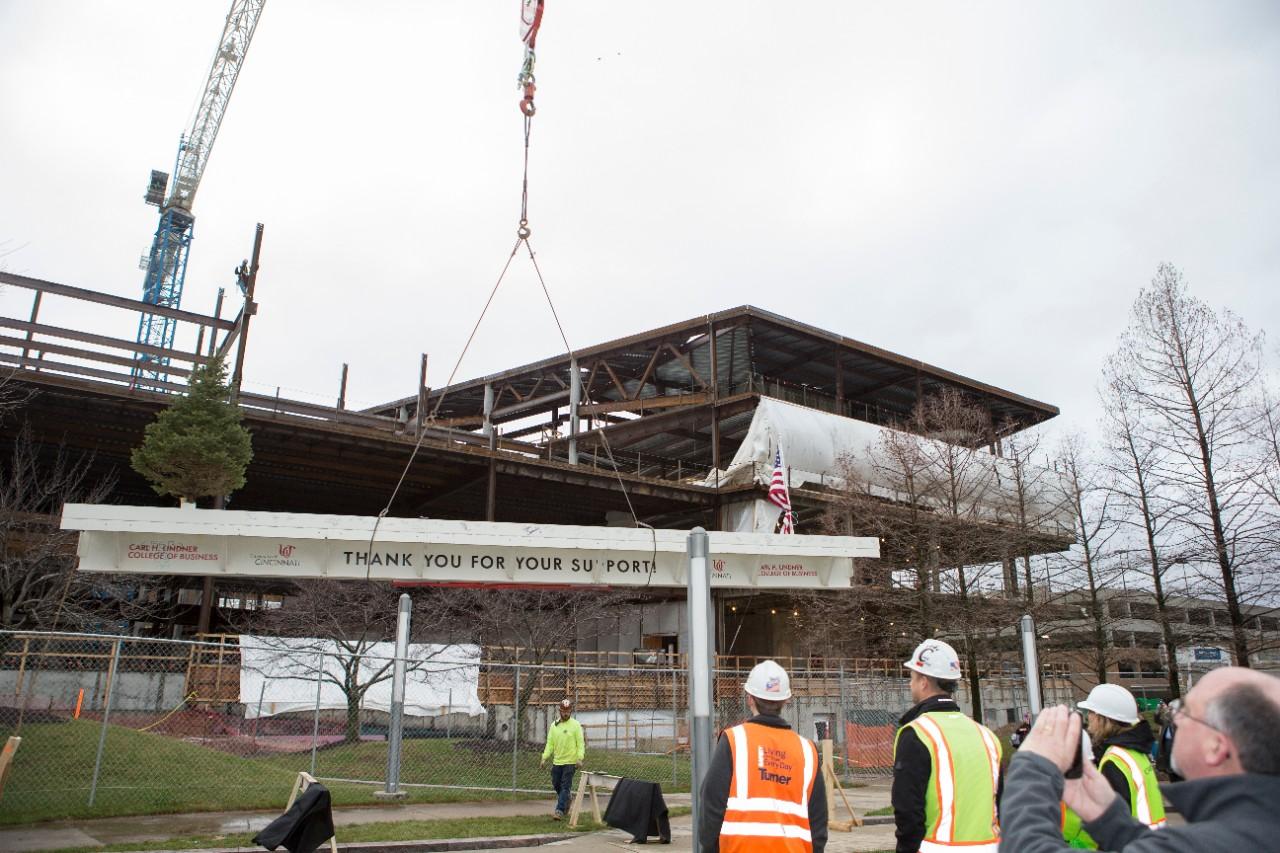 A crane slowly hoists the beam into position.