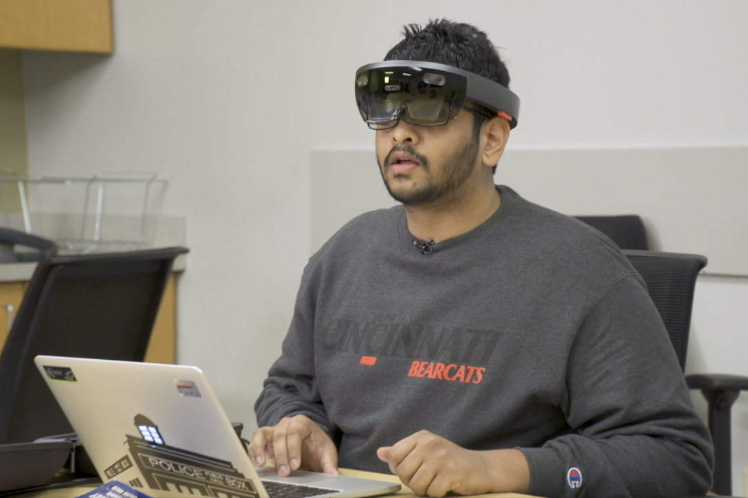 UC graduate research assistant Arjun Chiddarwar demonstrates the augmented reality system. (Photos by Paul Grundy)