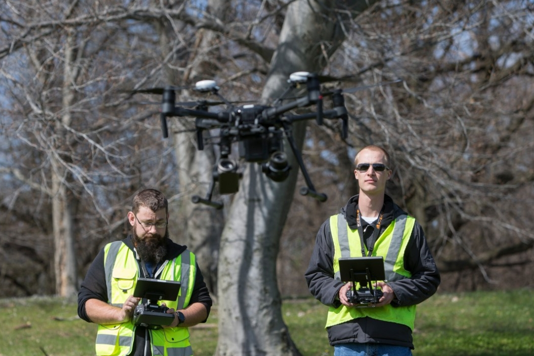 UC research associate Bryan Brown, left, and UC engineering student Austin Wessels work together to operate the drone. One navigates the drone in space while the other manipulates the cameras.