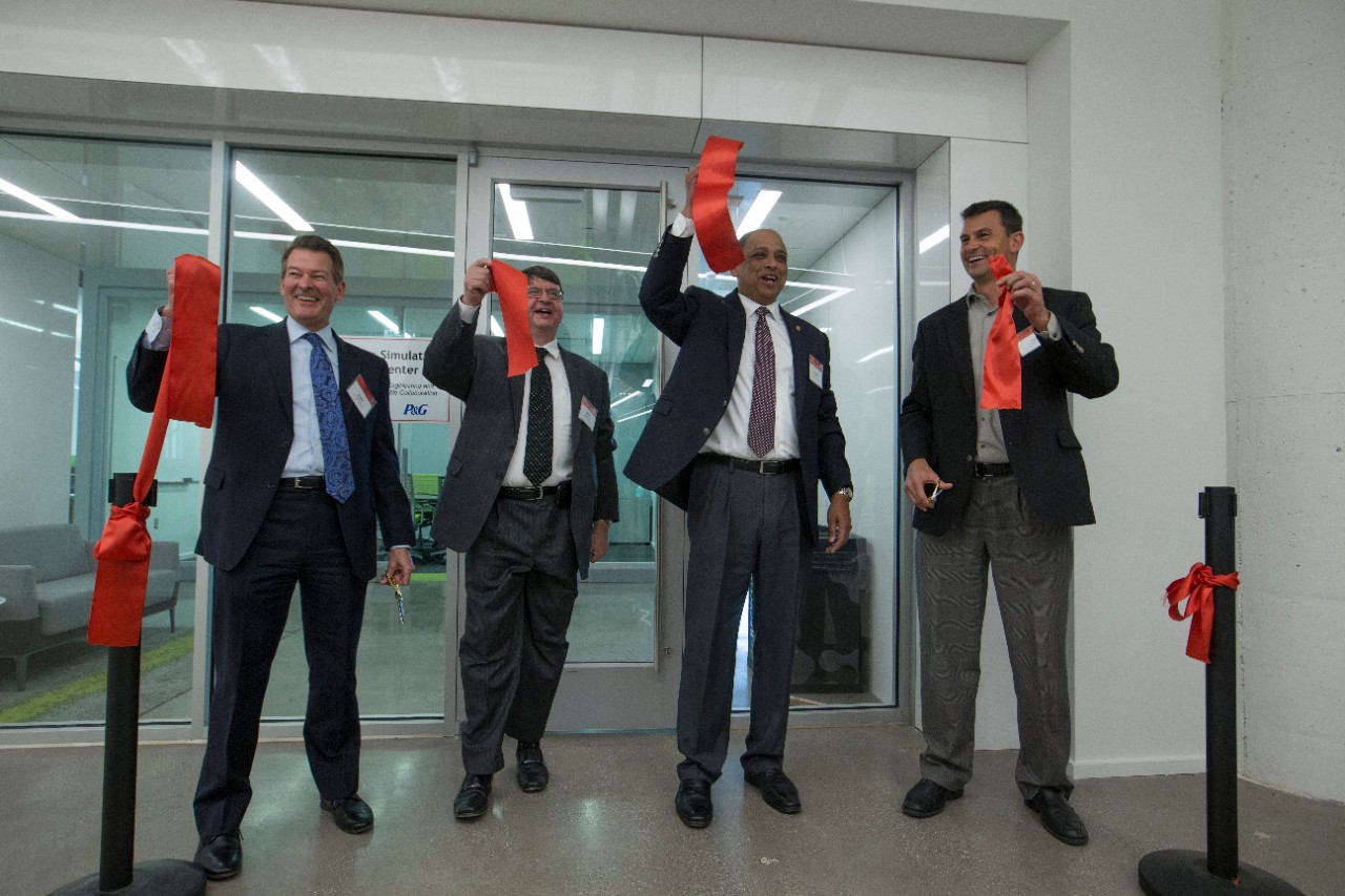 UC and P&G leaders hold up the cuttings of the red ribbon at the conclusion of the ribbon cutting ceremony.