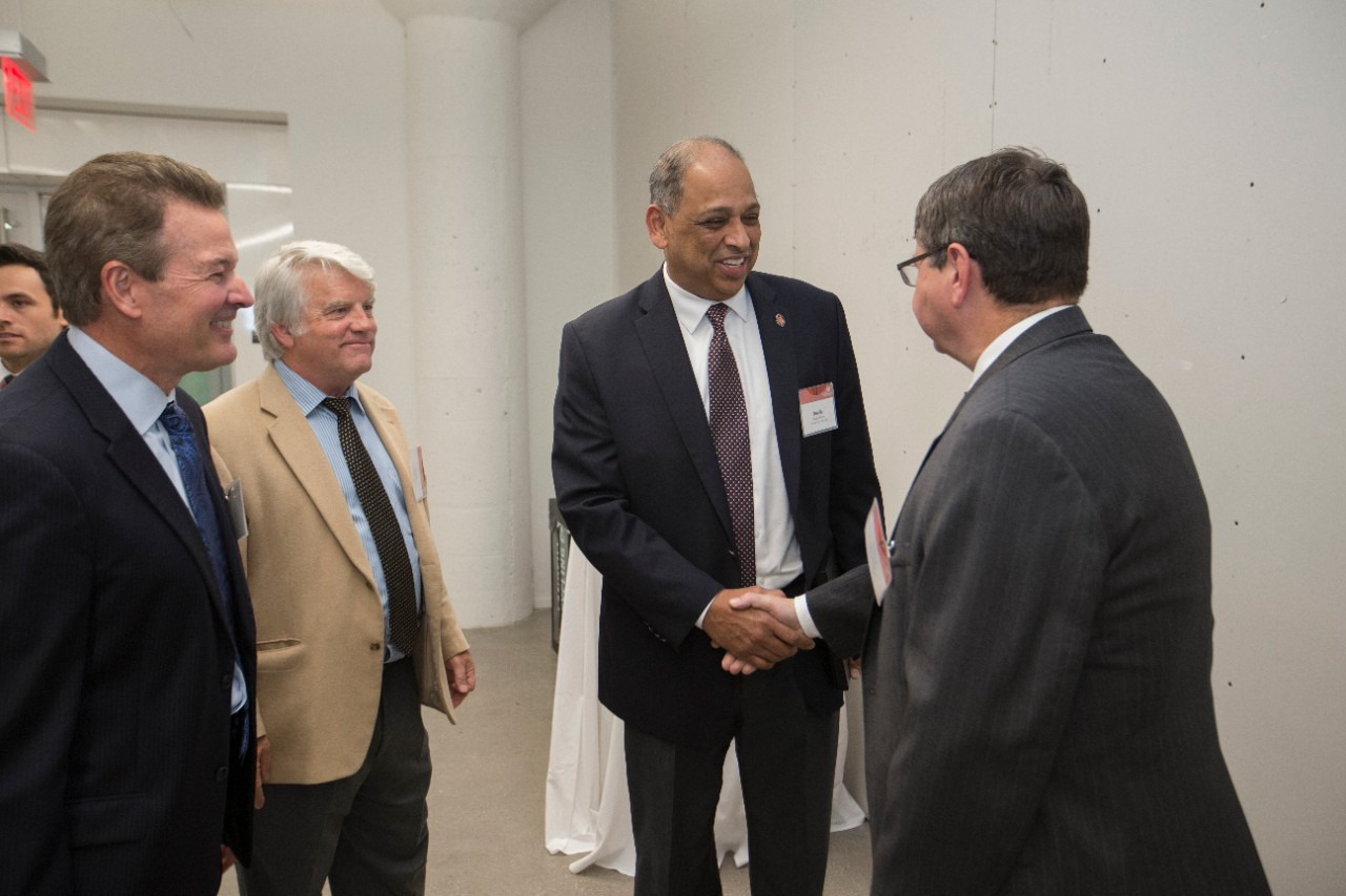 UCRI President David Adams and P&G site manager Fred Murrell, left, look on as UC President Neville Pinto shakes hands with P&G vice president Gerard Baillely.