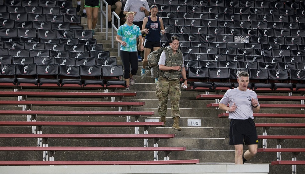 Several participants run down stairs, including a woman wearing fatigues and a large backpack.