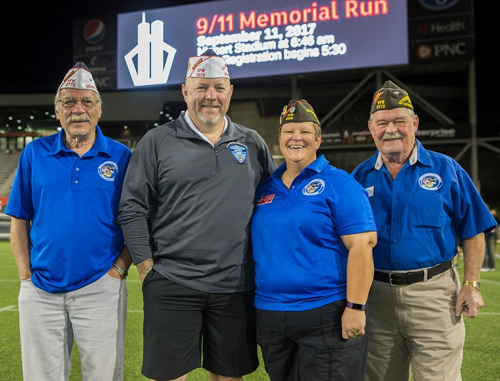 Three male and one female veteran pose in front of the video board at Nippert Stadium.