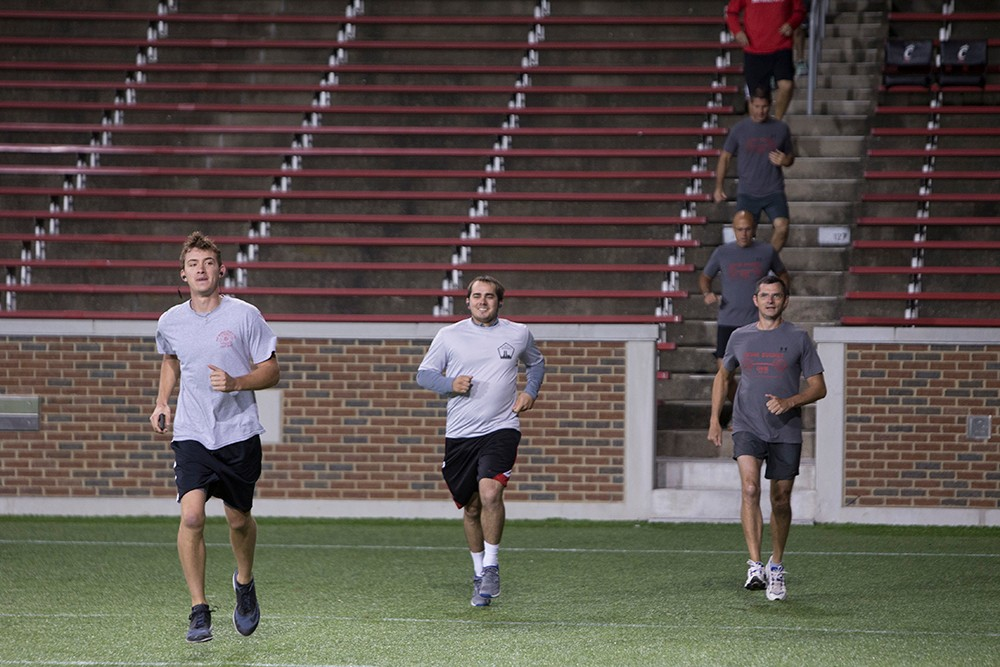 Several young men run across the field at Nippert Stadium.