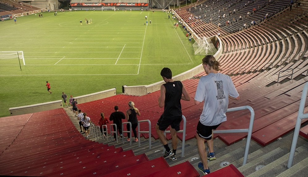A line of participants running down a flight of stairs at Nippert Stadium.