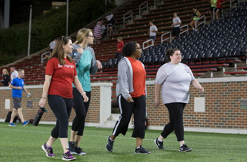 Four women walk along the sidelines of the field at Nippert Stadium.