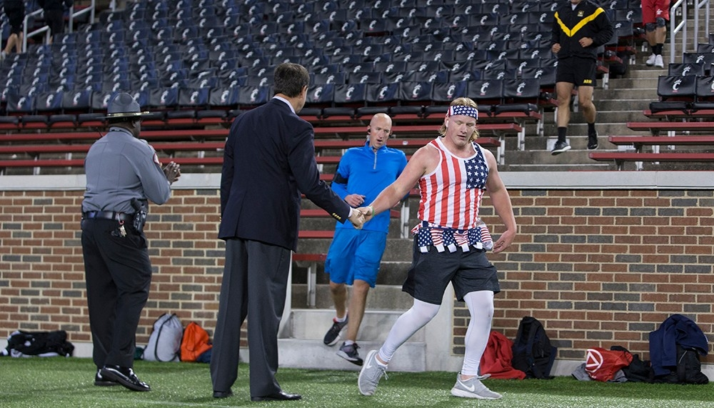 A young man wearing a patriotic bandana and tank top shakes hands with a man as he reaches the bottom of a flight of stairs.