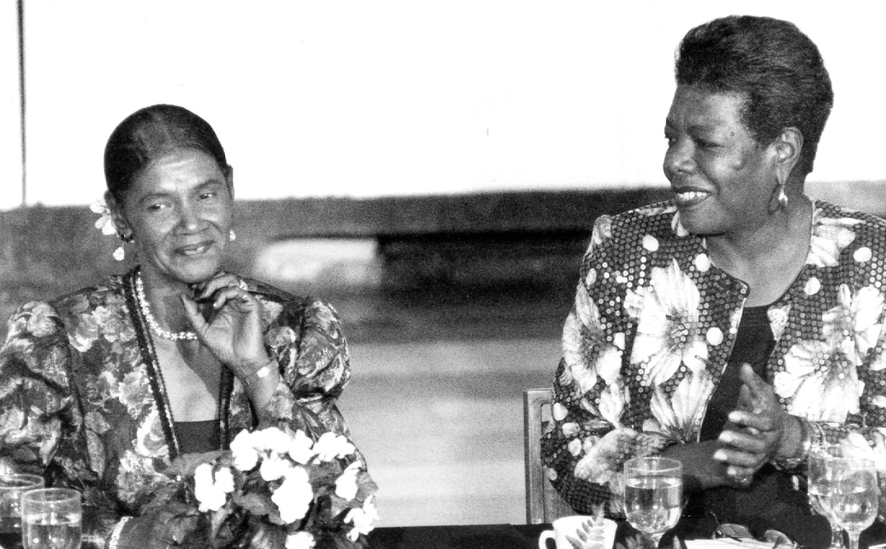 Maya Angelou, right, applauds for Jean Turner at a dinner honoring Turner's late husband, Darwin T. Turner