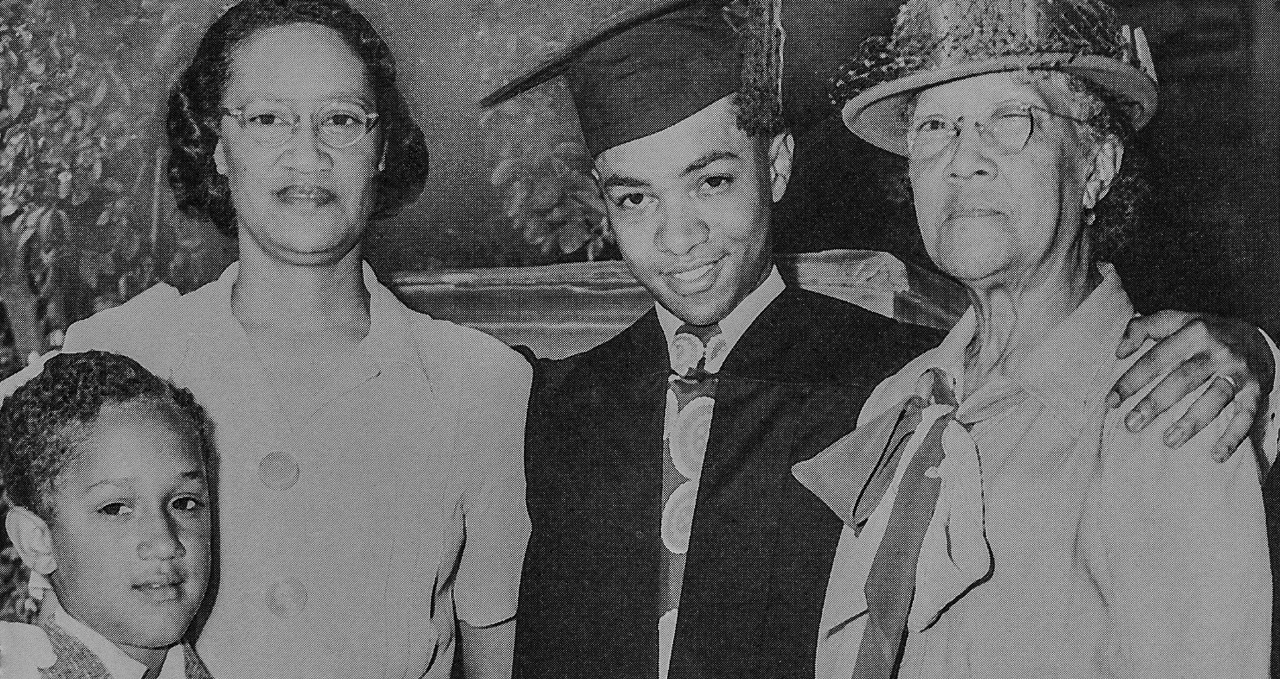 Darwin T. Turner, wearing his cap and gown, poses for the camera with relatives