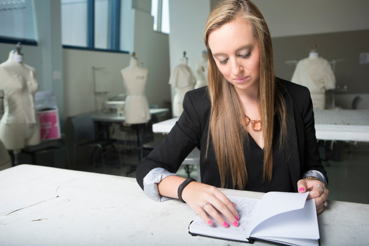 UC DAAP alum sits at a table in a fashion design studio reading a journal