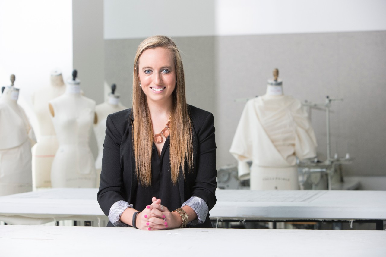 UC alum Megan Sullivan sits in a fashion design studio.
