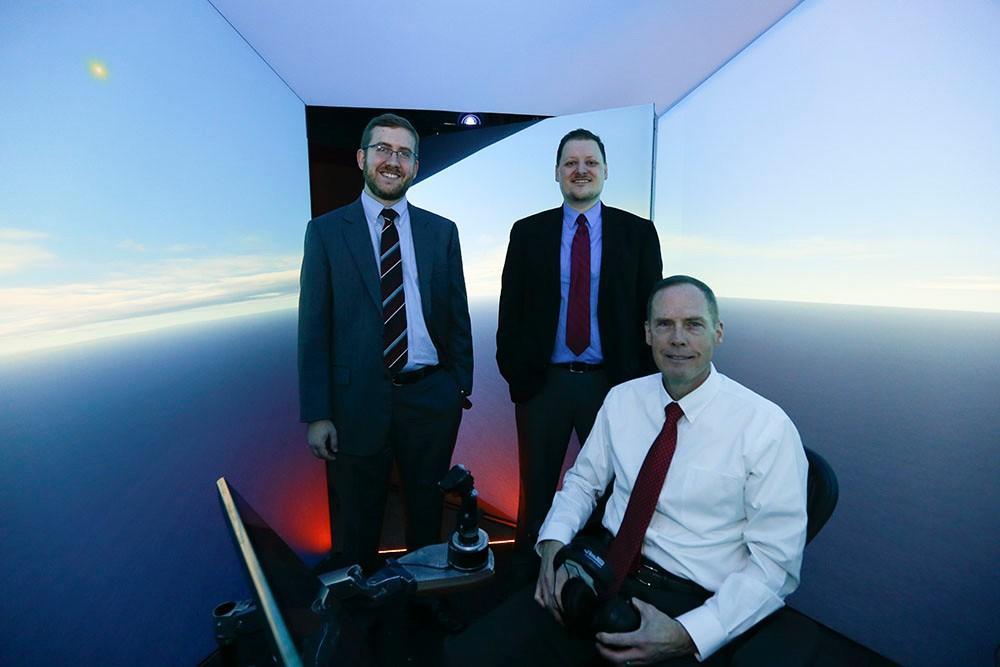 Nick Ernest, David Carroll and Gene Lee in flight simulator.