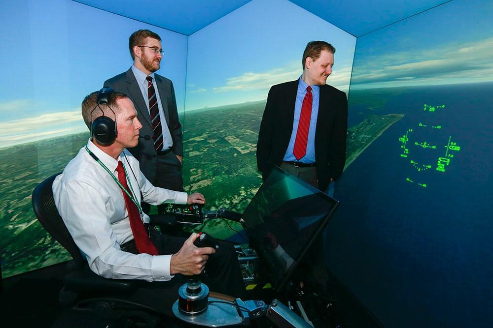 Nick Ernest, David Carroll and Gene Lee in a flight simulator.