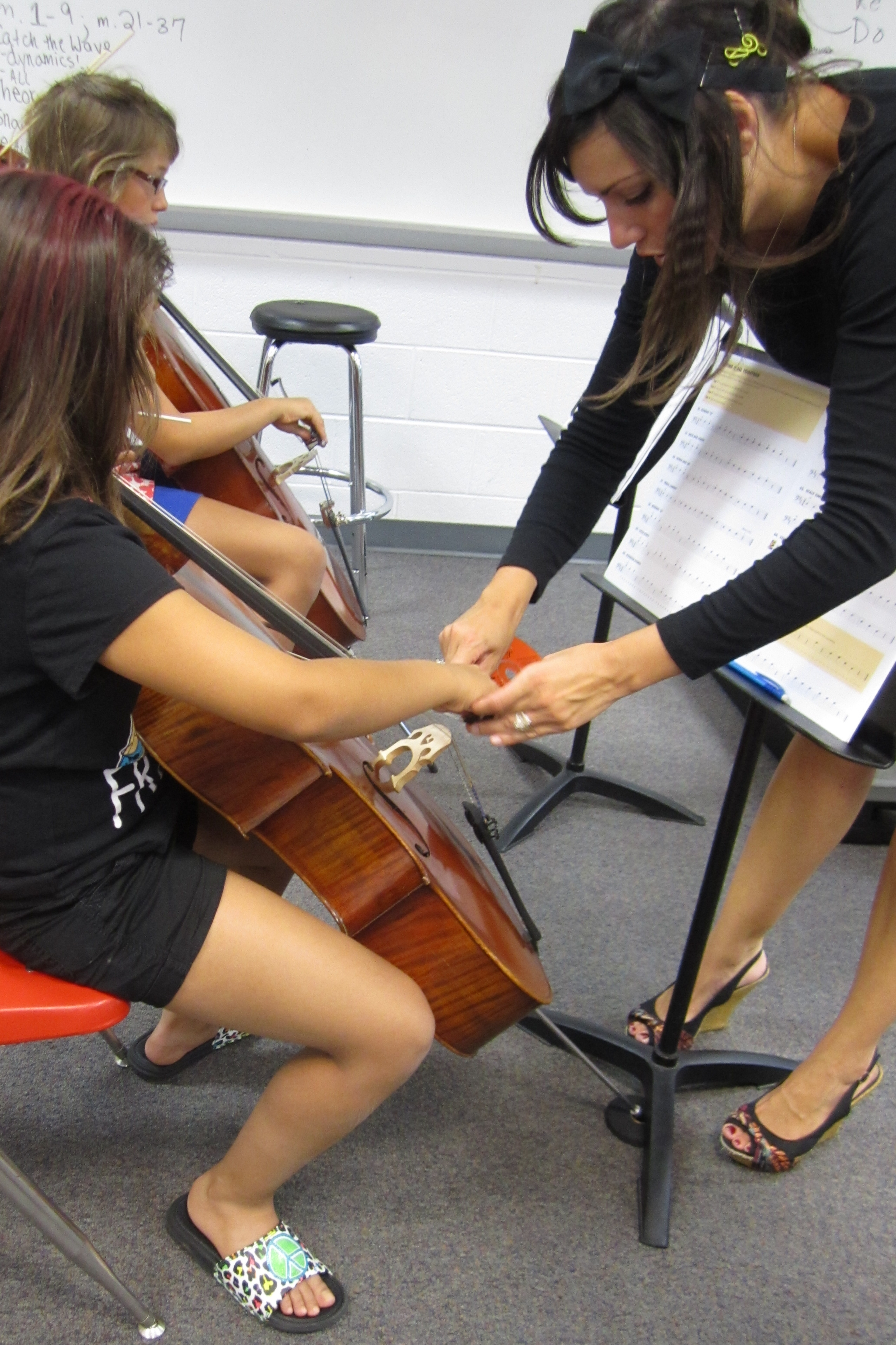 Angela Ammerman instructs a girl one-on-one how to hold a bow to play her instrument.