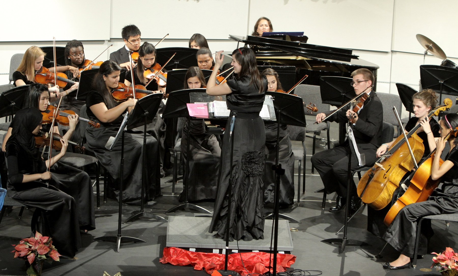 UC graduate Angela Ammerman leading an orchestra.