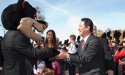 Bearcat shakes Santa Ono's hand while the Bearcat band plays