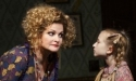 Faith Prince leans over to listen to one of the orphans in the show Annie.