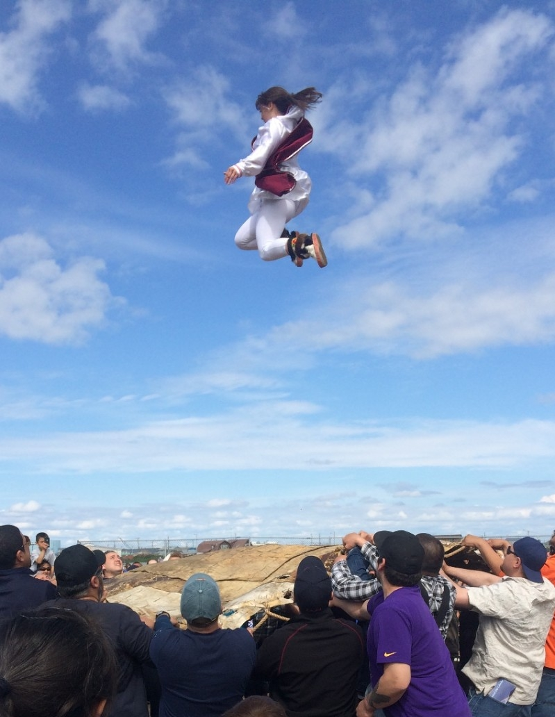 A girl in Kotzebue, Alaska, takes part in a traditional Eskimo blanket toss as part of a summer festival.
