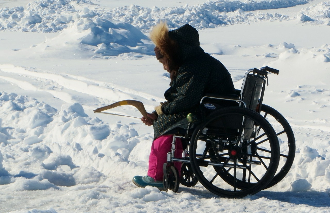 A resident of Kotzebue, Alaska, ice-fishes from a wheelchair.