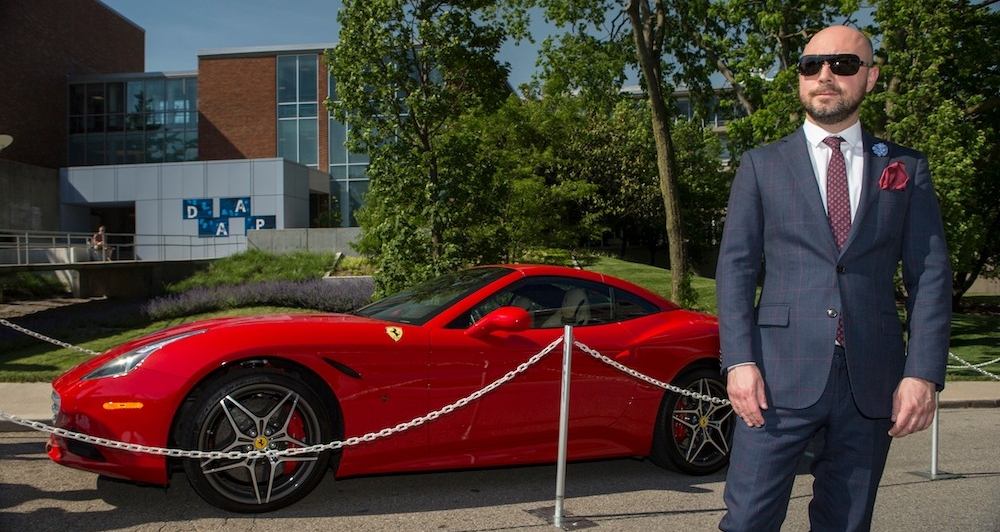 DAAP School of Design Director Gjoko Muratovski wears a suit and sunglasses standing by a red Ferrari