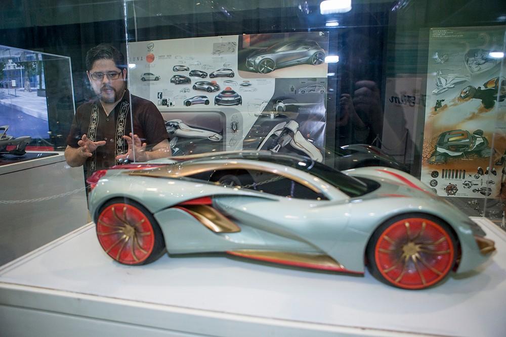 Professor Islas-Muñoz stands among DAAP students' futuristic car concepts at the Cincinnati Auto Expo.