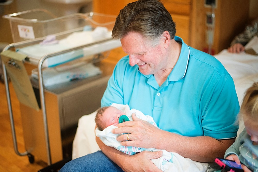 Lenny Robinson holds his grandson, Baehr, in the hospital.