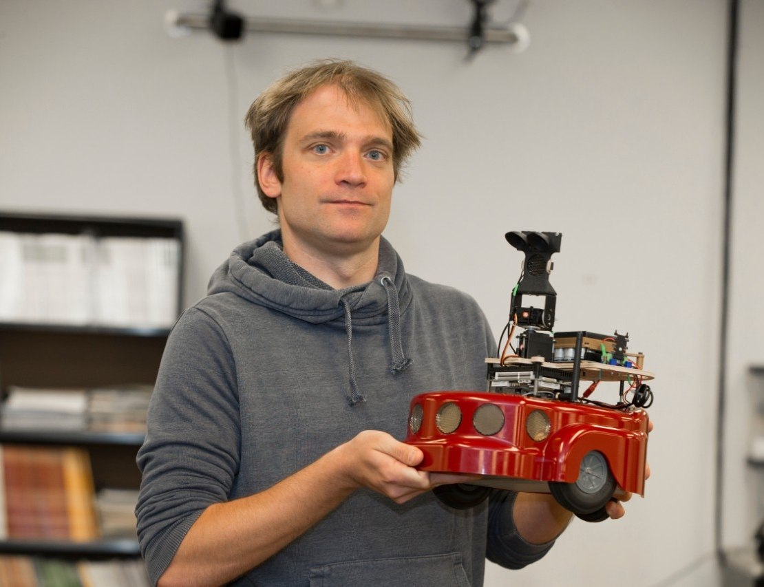 UC professor Dieter Vanderelst holds up his bat-inspired robot in a UC robotics lab. The lab is outfitted with dozens of motion-capture cameras to study movement.
