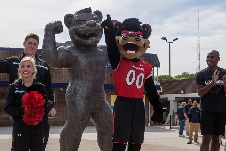 University of Cincinnati cheerleaders and mascot stand next to a new statue of the Bearcat mascot.
