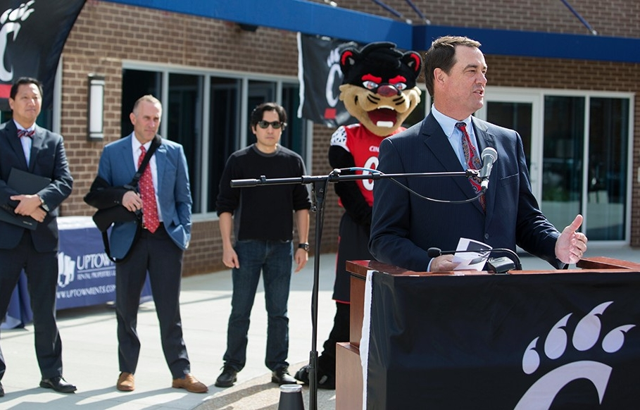 University of Cincinnati Athletics Director Mike Bohn stands at a podium to speak as part of a statue unveiling ceremony.