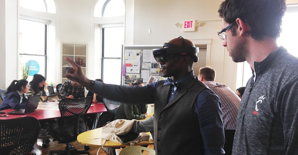 A man in a vest and bowtie uses a VR headset and points with his finger as another man looks on.