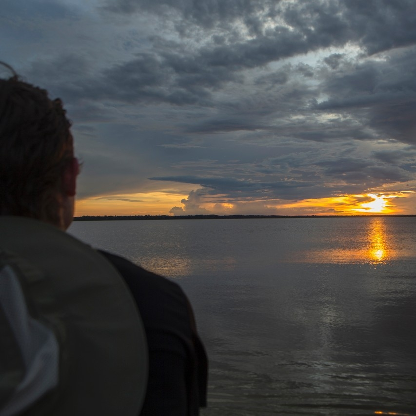 Student profile looking off into a sunset over the Amazon river.