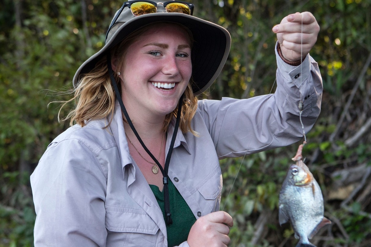 Student holds a piranha on a fishing line.