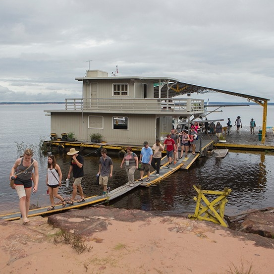 Students walk across a platform from a houseboat onto land.