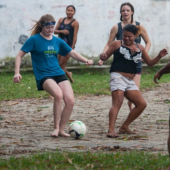 Student kicks a soccer ball during a game with the locals.