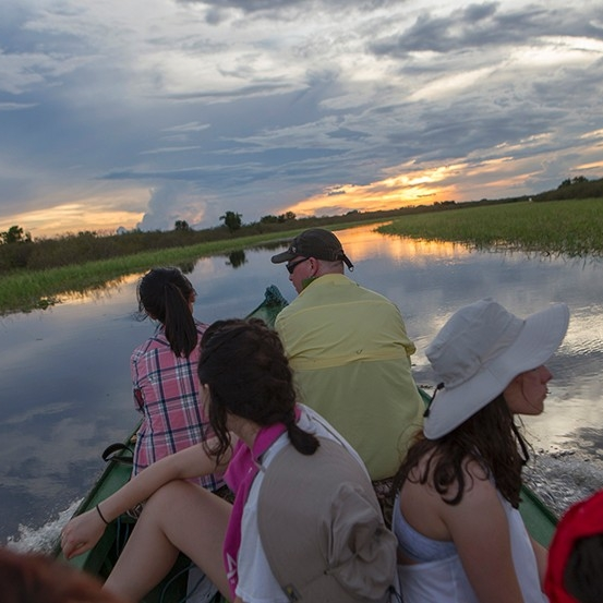 Students on a boat travel down the Amazon toward a beautiful sunset.