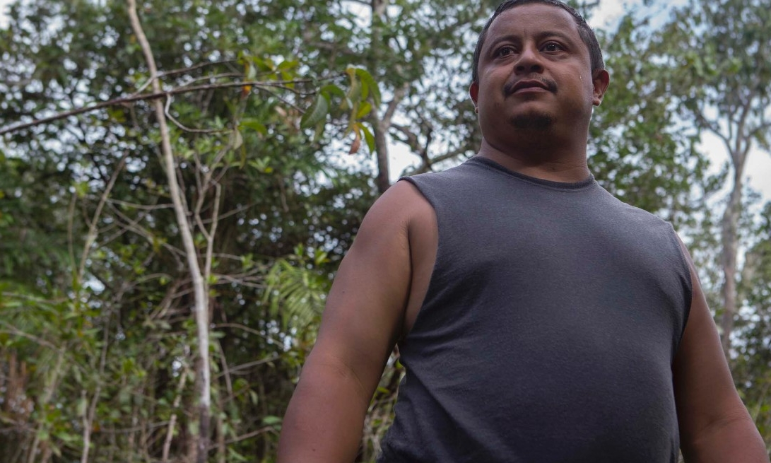 Brazilian man stands on the banks of the Amazon.