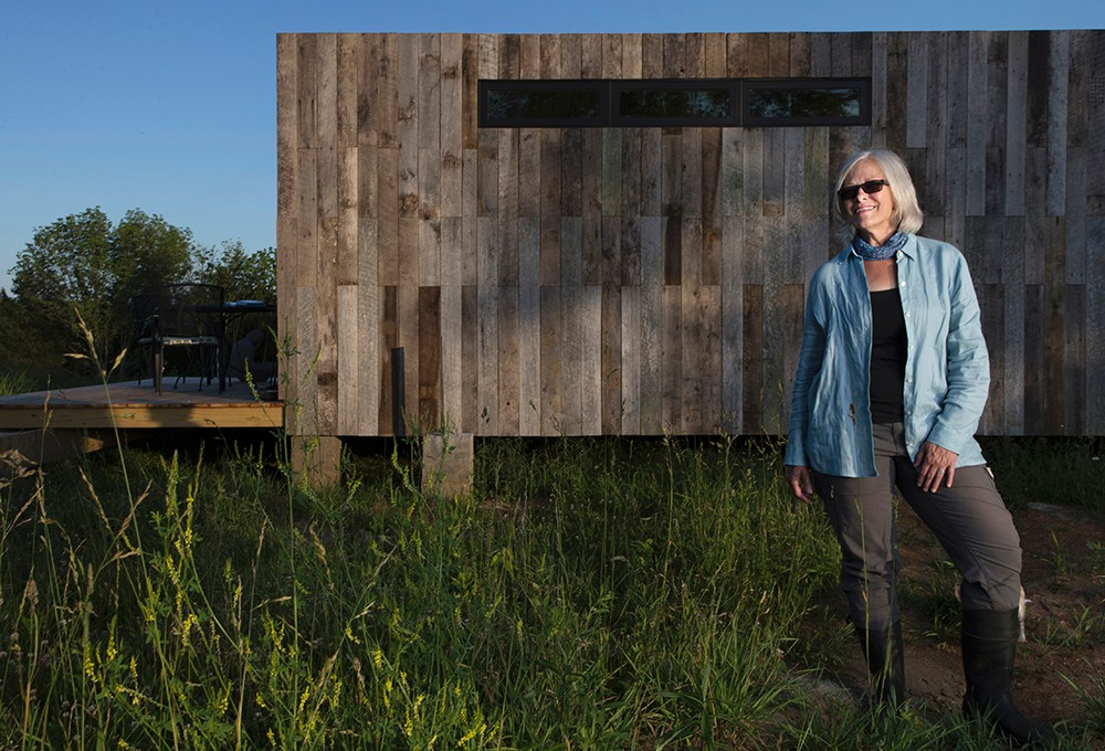 Land steward Adrienne Cassel stands in front of her tiny house on the Kamama Prairie.
