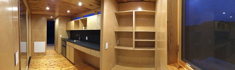 A panoramic view of the interior of the tiny house, featuring detailed woodwork.