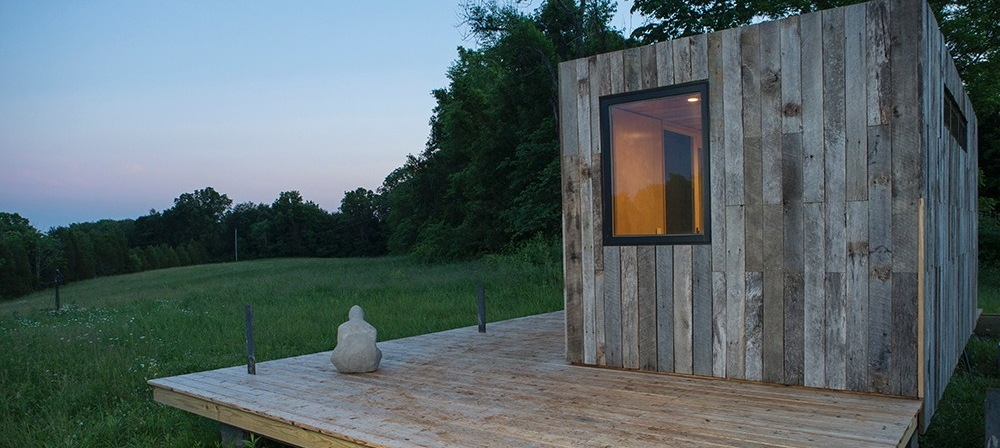 A side view of the tiny house and deck on Kamama Prairie as the sun sets.