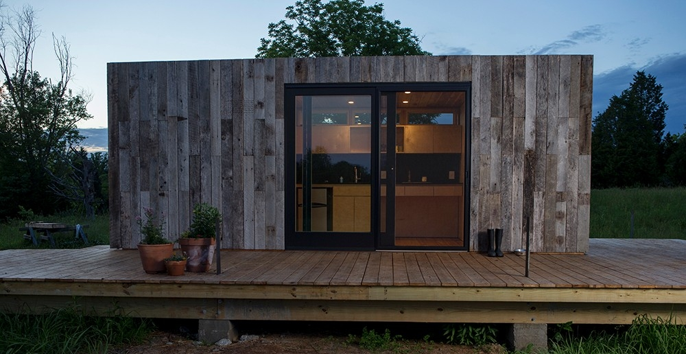 A tiny house sided with reclaimed wood is lit up from within as the sun sets on the Kamama Prairie