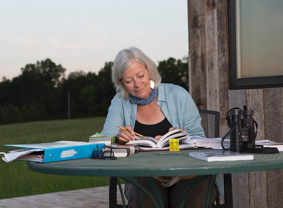 Land steward Adrienne Cassel sits at a table on a deck in the Kamama Prairie doing school work.
