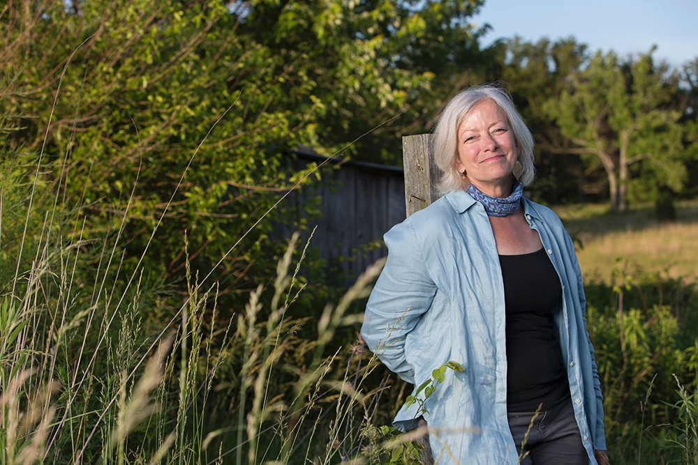Adrienne Cassel poses in the middle of the Kamama Prairie surrounded by trees and greenery.