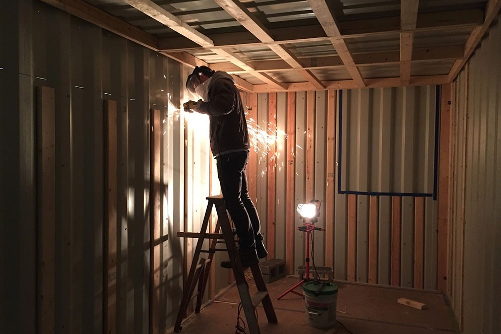 A student welds inside the under-construction tiny house, made from a shipping container.