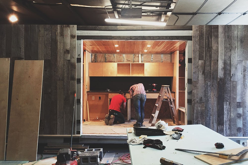 Students work on the tiny house's kitchen as the under-construction home sits in a workshop.