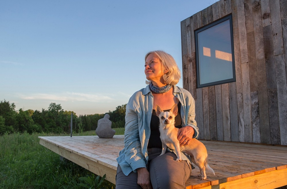 Adrienne Cassel sits with a dog on the deck of her DAAP-constructed tiny house at the Kamama Prairie