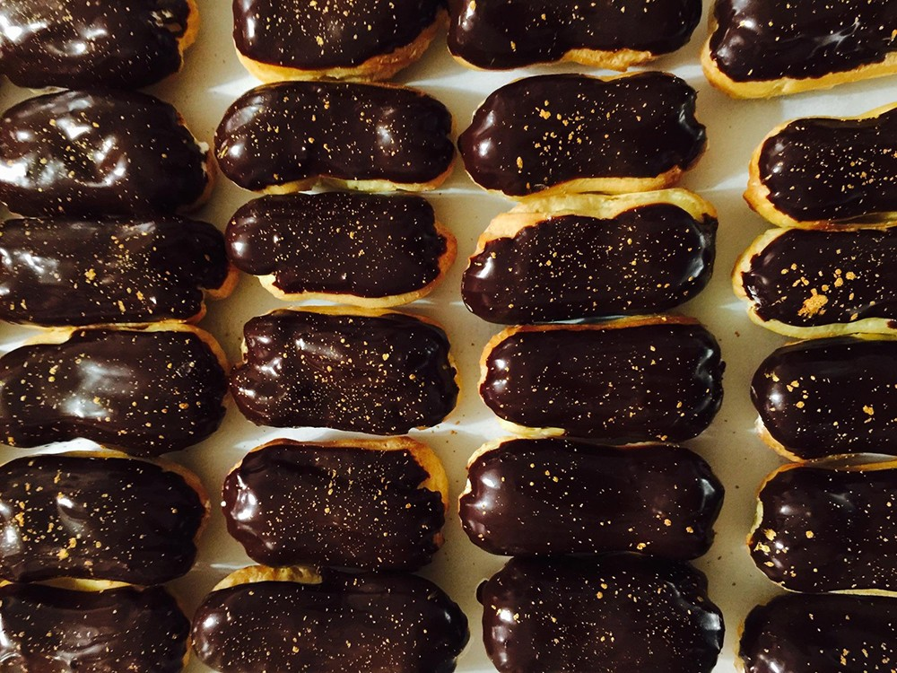 Rows of chocolate-iced eclairs made by James Avant