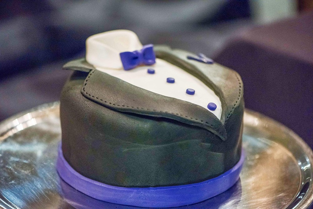 A round cake from OCD Cakes is iced to resemble a tuxedo