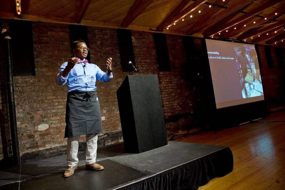 James Avant stands onstage addressing the audience at the Big Pitch competition.