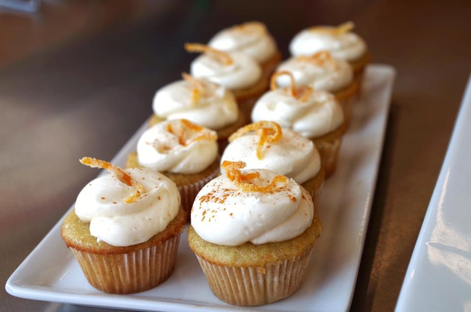 Two rows of cupcakes topped with white icing and candied orange peels, from OCD Cakes.